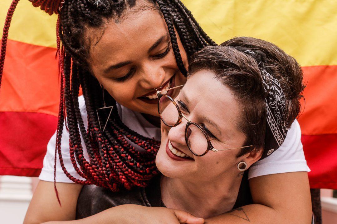Casal com bandeira LGBTQ+ ao fundo